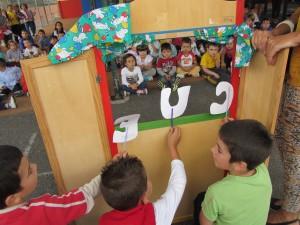 Comienza el teatro de marionetas. Los niños y las niñas de Infantil leen el título de la obra.