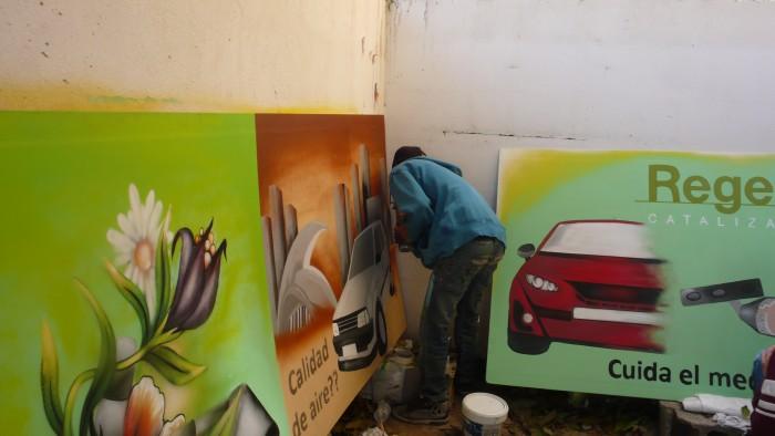 Alumno realizando una pintura mural